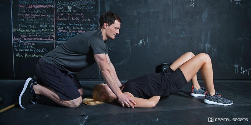 Mobility Training / Übung mit dem Partner. Person 1 drückt Schultern der auf dem Boden liegenden 2. Person