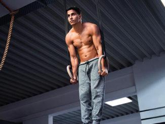 Mann muscle up Haltung auf Turnringen