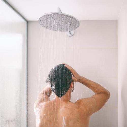 Mann duscht am Morgen