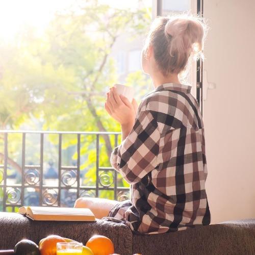 Frau sitzt am Morgen am offenen Fenster
