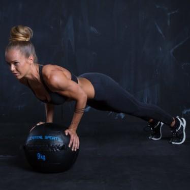 Frau macht Push Up auf dem Medizinball
