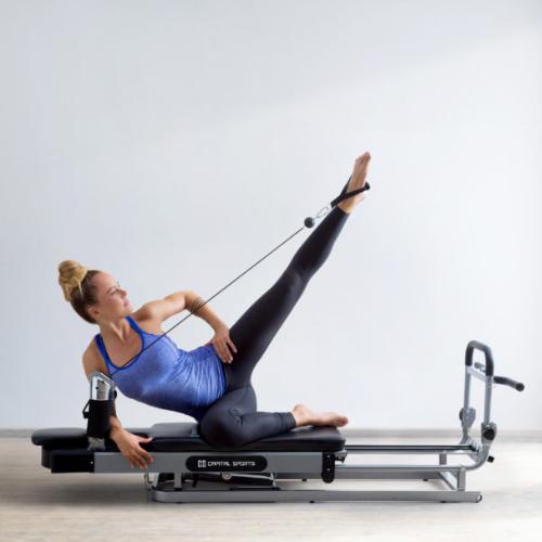 Frau auf Pilates Reformer Bein ausgestreckt