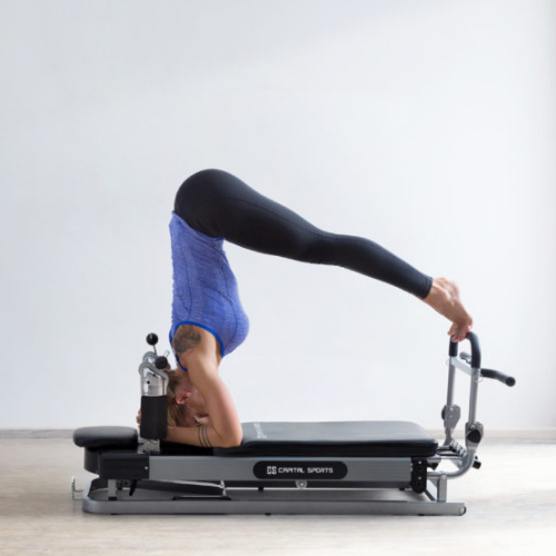 Frau auf Pilates Reformer Kopfstand