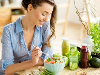 Frau isst einen Salat - symbolisch für gesund essen